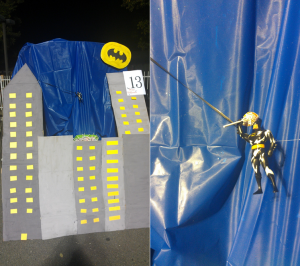 Photo of cardboard buildings and toy batman holding a lollipop.