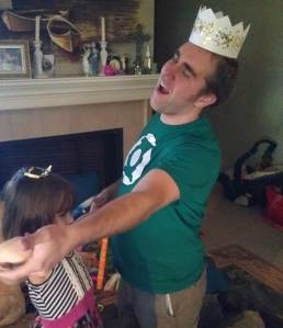 Husband with paper crown dancing with little girl with a princess crown