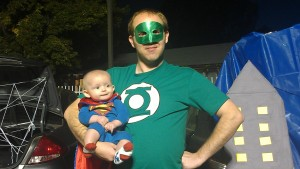 Husband dressed up as Green lantern holding baby boy dressed up as superman.
