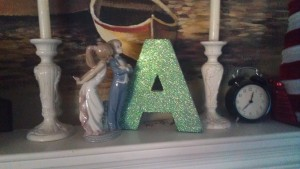 A large glittery letter A on a mantel