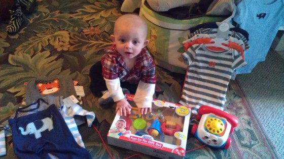 Baby surrounded by toys and clothes